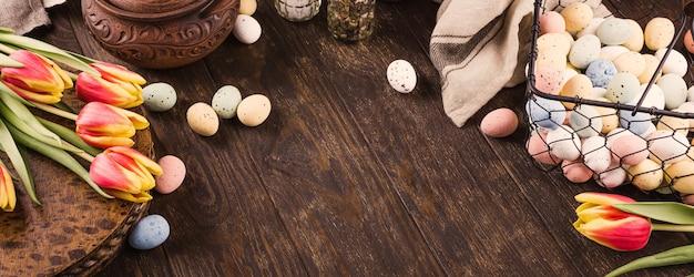 Frohe ostern oberfläche mit tulpen und bunten wachteleiern im metallkorb auf holzoberfläche. speicherplatz kopieren