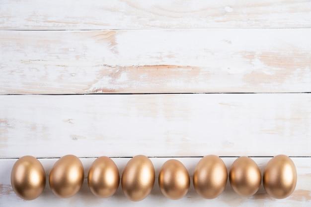 Frohe ostern! rudern sie goldene eier ostern mit auf weißem hölzernem hintergrund