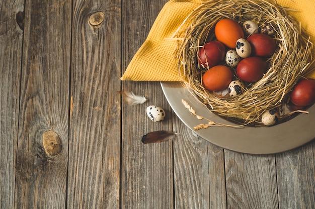 Frohe ostern tisch. ostereier in einem nest auf einer metallplatte auf einem holztisch. frohe ostern konzept