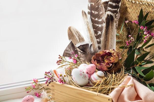 Frohe ostern tisch. rosa ostereier in einem nest mit blumendekorationen und federn nahe dem fenster