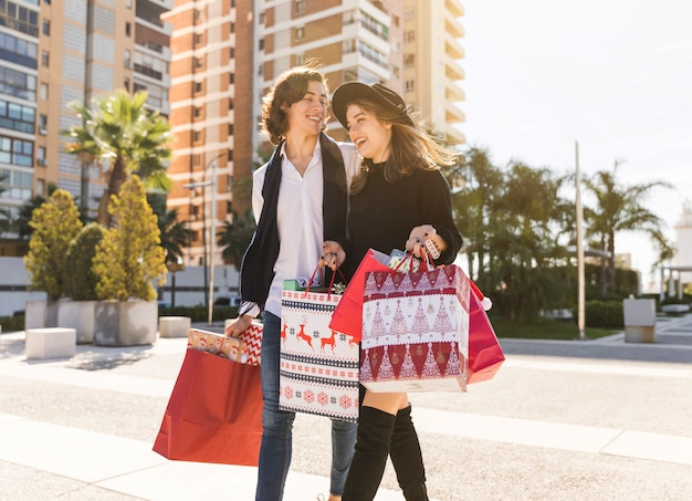 Frohe paare, die mit weihnachtseinkaufstaschen gehen