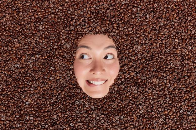 Frohe positive junge frau, die sich auf die linken bisslippen konzentriert, zeigt weiße zähne, die von kaffeebohnen umgeben sind, und genießt ein angenehmes aroma, das ein leckeres getränk zubereiten wird. kreative aufnahme