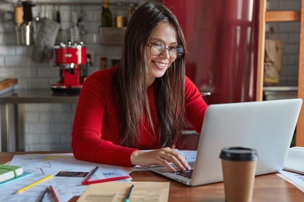 Frohe professionelle brünette buchhalterin macht entfernte arbeit, tastaturen auf laptop, sitzt am küchentisch mit papieren, trägt transparente brille für gute sicht, trinkt kaffee zum mitnehmen
