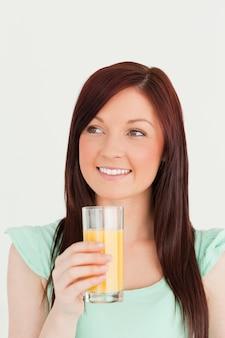 Frohe red-haired frau, die ein glas orangensaft in der küche genießt