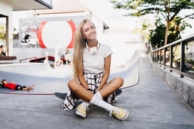 Frohe schlanke frau, die nach dem training auf longboard sitzt. außenporträt des hübschen blonden weiblichen modells, das im skatepark am wochenende aufwirft.