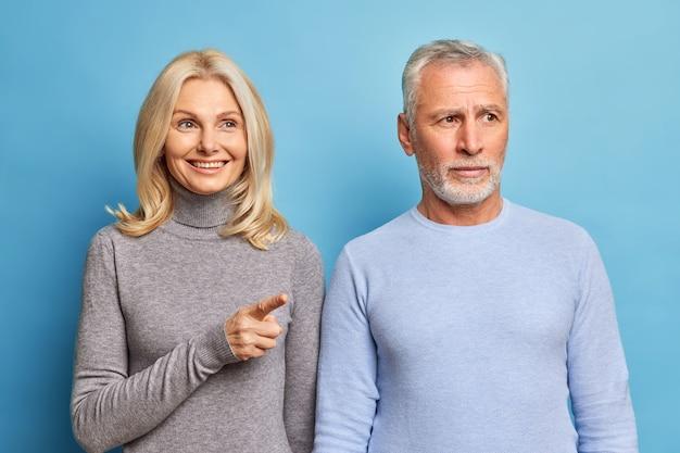 Frohe schöne frau mittleren alters zeigt zeigefinger in die ferne und zeigt dem ehemann etwas, der sich irgendwo mit ernstem ausdruck konzentriert