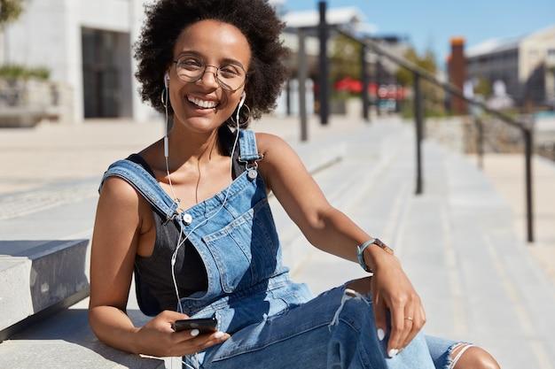 Frohe schwarze entspannte junge frau hört lieblingsmusik oder radiosendung, lacht glücklich, trägt freizeitkleidung, transparente brille, modelle im freien auf der straße.