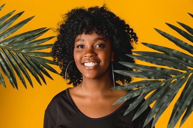 Frohe schwarze junge frau mit tropischen blättern im studio