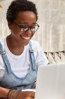 Frohe schwarze studentin bereitet sich auf die universitätsprüfung vor und arbeitet im café