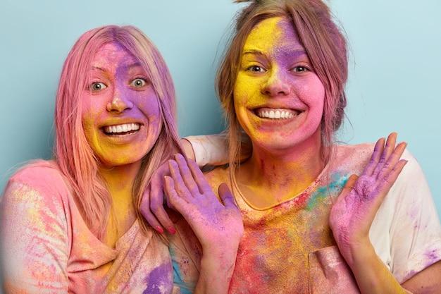 Frohe schwestern lächeln glücklich, beeindruckt von einer schönen zeit zusammen, haben freudige gesichtsausdrücke, feiern das holi-festival mit farben, zeigen bunte hände, bedeckt mit farbigem puder. emotionskonzept