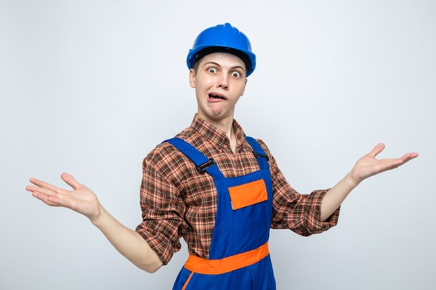 Frohe, sich ausbreitende hände junger männlicher baumeister, der uniform trägt