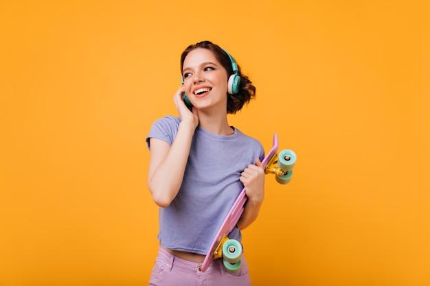 Frohe skateboarderin, die ihr lieblingslied hört. innenaufnahme des glückseligen lockigen mädchens mit der gewellten frisur, die ihr rosa longboard hält.