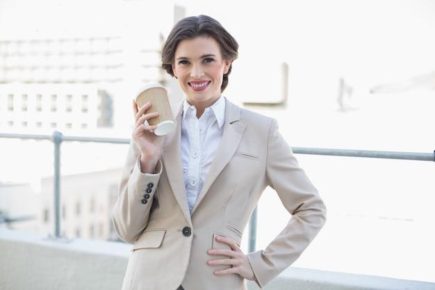 Frohe stilvolle braune behaarte geschäftsfrau, die eine kaffeetasse hält