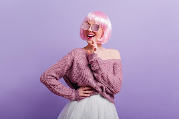 Frohe stilvolle frau mit rosa haaren glücklich lachendes innenporträt des lächelnden ekstatischen mädchens, das in der selbstbewussten haltung auf lila wand steht.
