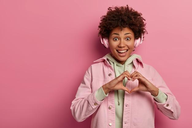 Frohe teenager-frau macht herzgeste über der brust, drückt zuneigung aus