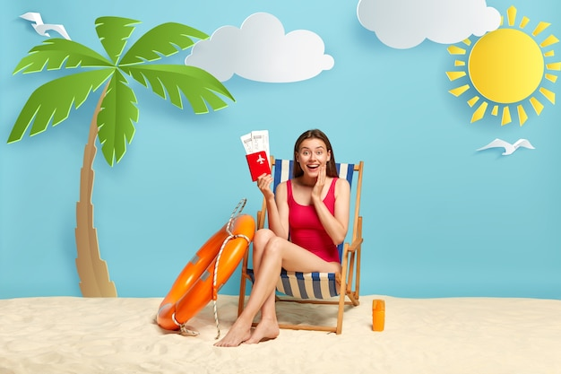 Frohe weibliche reisende sitzt auf strandkorb, hält pass mit flugtickets