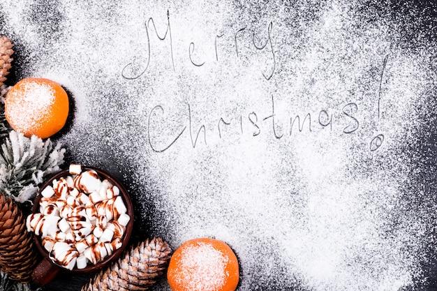 Frohe weihnacht-handgemachter text auf schnee. weihnachtslebensmittel-süßer eibisch mit schokolade in brown-schale