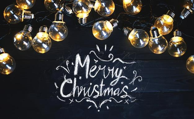 Frohe weihnacht-typografie-glühlampen auf schwarzem holz