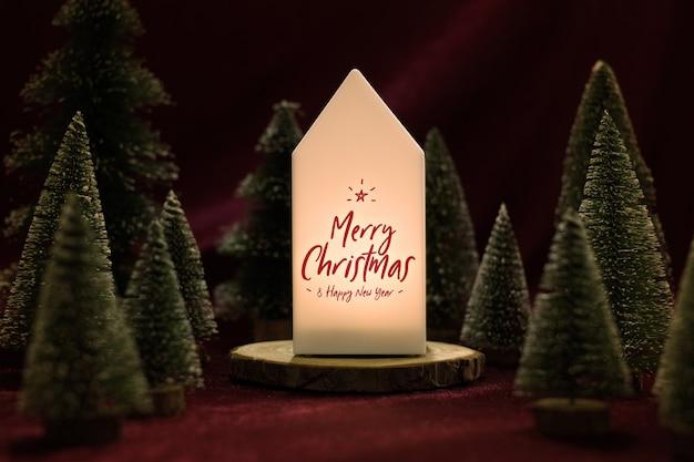 Frohe weihnachten auf hauptlampe mit weihnachtsbaum auf samtgewebetisch in der dunklen nacht