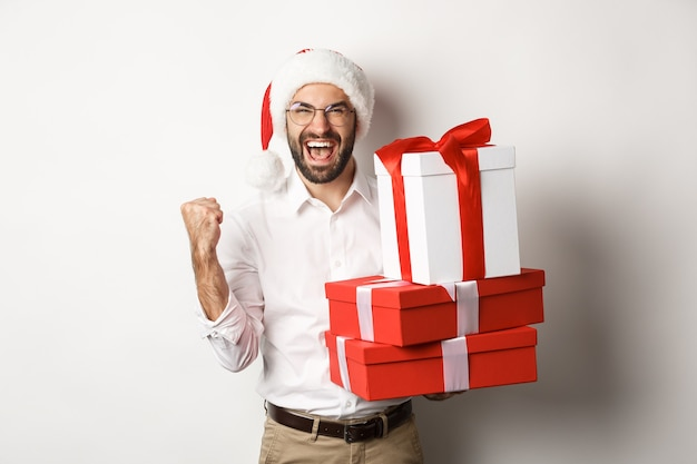 Frohe weihnachten, feiertagskonzept. aufgeregter mann, der weihnachtsgeschenke empfängt und sich freut, weihnachtsmütze trägt und neujahr feiert
