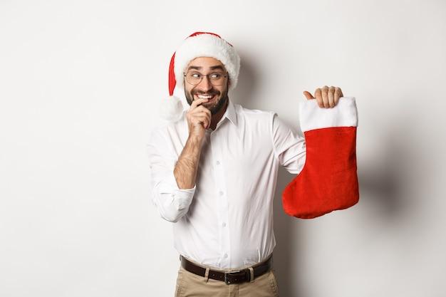 Frohe weihnachten, feiertagskonzept. erwachsener mann, der glücklich und neugierig auf weihnachtssocke schaut, geschenke erhält, weihnachtsmütze tragend