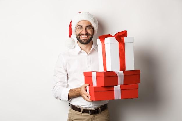 Frohe weihnachten, feiertagskonzept. glücklicher junger mann, der lächelt, geschenke in kisten hält und weihnachtsmütze trägt
