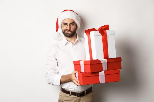 Frohe weihnachten, feiertagskonzept. nachdenklicher mann, der weihnachtsgeschenke hält und misstrauisch in die kamera schaut, neujahr feiert