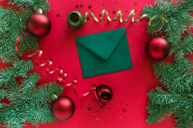 Frohe weihnachten frohes neues jahr konzept. weihnachtskomposition. weihnachtsbrief, kugeln, tannenzweige auf roter oberfläche. draufsicht, flach liegen.