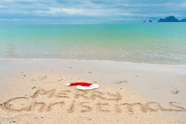 Frohe weihnachten geschrieben auf tropischen strandsand