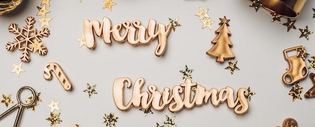 Frohe weihnachten gold glänzender text mit luxus-weihnachtsdekorationsgegenständen auf weißem tisch