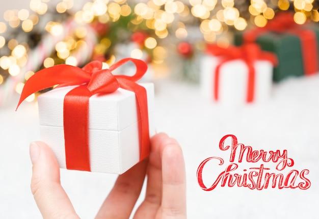 Frohe weihnachten grußkarte mit einer frauenhand, die eine geschenkbox hält