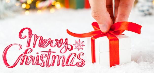 Frohe weihnachten grußkarte mit einer mannhand, die eine geschenkbox mit rotem band auf dem schnee und verschwommenen lichtern hält