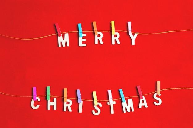 Frohe weihnachten grußnachricht mit wäscheklammern auf roter oberfläche
