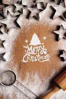 Frohe weihnachten-inschrift aus mehl auf einem holztisch