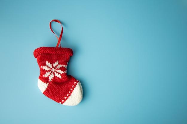 Frohe weihnachten-konzept: neugeborene socke des roten babys auf blauem hintergrund