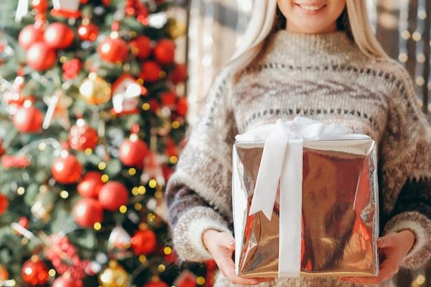 Frohe weihnachten. kurzer schuss der dame im kuscheligen pullover, der große glänzende geschenkbox hält, lächelnd. verwischen sie dekorierten tannenbaum in
