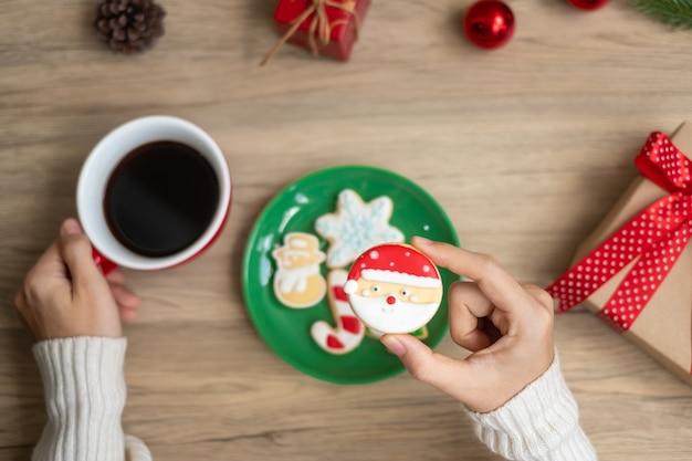 Frohe weihnachten mit der frauenhand, die kaffeetasse und hausgemachtes plätzchen auf dem tisch hält. weihnachtsabend-, party-, feiertags- und frohes neues jahr-konzept