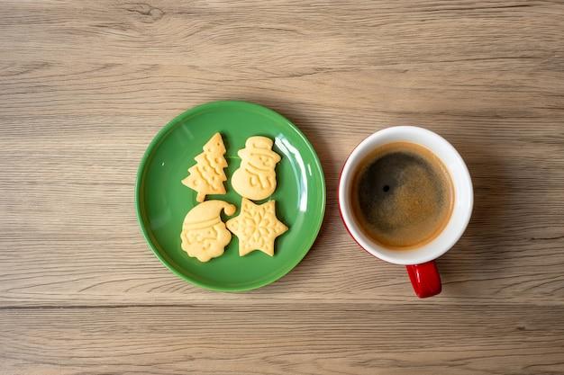 Frohe weihnachten mit hausgemachten keksen und kaffeetasse auf holztischhintergrund. weihnachtsabend-, party-, feiertags- und frohes neues jahr-konzept