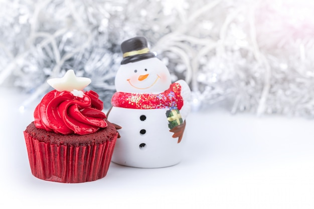 Frohe weihnachten mit rotem kleinem kuchen und schneemann