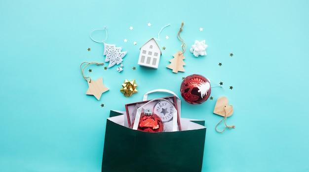 Frohe weihnachten mit verzierungsstützenelement und einkaufstasche auf farbhintergrund.