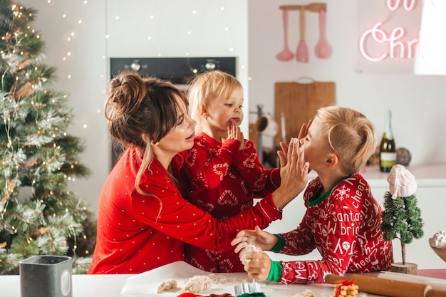 Frohe weihnachten. mutter und kinder backen weihnachtsplätzchen, machen sich mit mehl schmutzig, spielen spaß