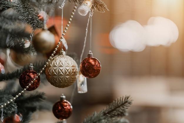 Frohe weihnachten, nahaufnahme von bunten bällen, geschenkbox und weihnachtsgrußbild-paketdekoration auf grünem weihnachtsbaumhintergrunddekoration während weihnachten und neujahr.