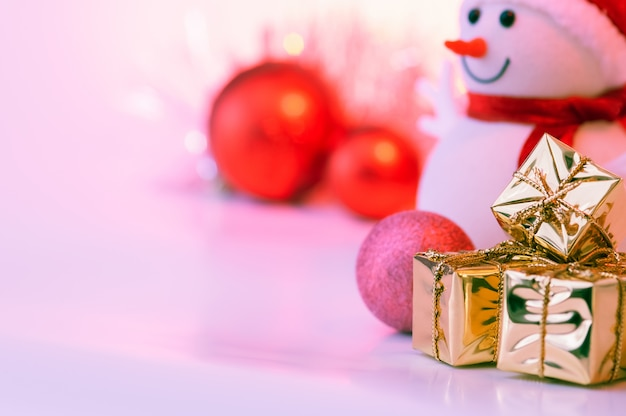Frohe weihnachten, neues jahr, schneemann, geschenke in den goldkästen und rote bälle auf einem rosa.