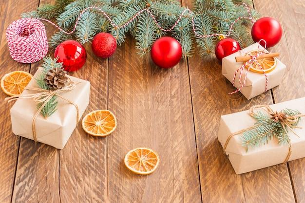 Frohe weihnachten-rahmen mit grüner kiefer aus echtem holz, bunten kugeln und anderen saisonalen sachen über einem alten hölzernen hintergrund.