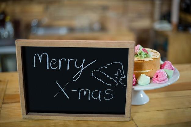 Frohe weihnachten schild mit kuchen an der theke