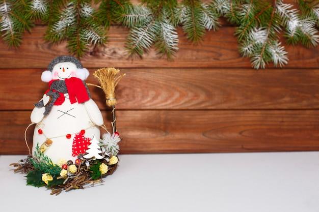 Frohe weihnachten schneemann. weihnachtsdekoration auf einem hölzernen hintergrund. grußkarte. weihnachtsdekoration.