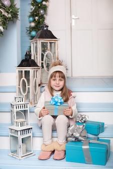 Frohe weihnachten, schöne feiertage! neues jahr 2020. kleines mädchen sitzt mit geschenken auf der veranda eines hauses für weihnachten dekoriert. kind sitzt auf der veranda für neujahr dekoriert. kind öffnet weihnachtsgeschenk.