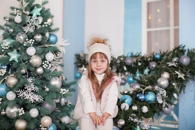 Frohe weihnachten, schöne feiertage! neujahr. kleines mädchen sitzt in der nähe von weihnachtsbaum auf der veranda des hauses. kind sitzt auf der zu weihnachten dekorierten terrasse. kind spielt im wintergarten und schmückt die veranda