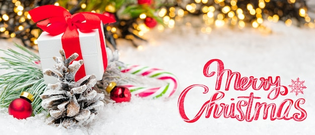 Frohe weihnachten schriftzug auf dem hintergrund der weihnachtsdekoration mit geschenkboxkegel