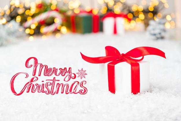 Frohe weihnachten schriftzug auf der grußkarte mit geschenkboxen lichter und schnee